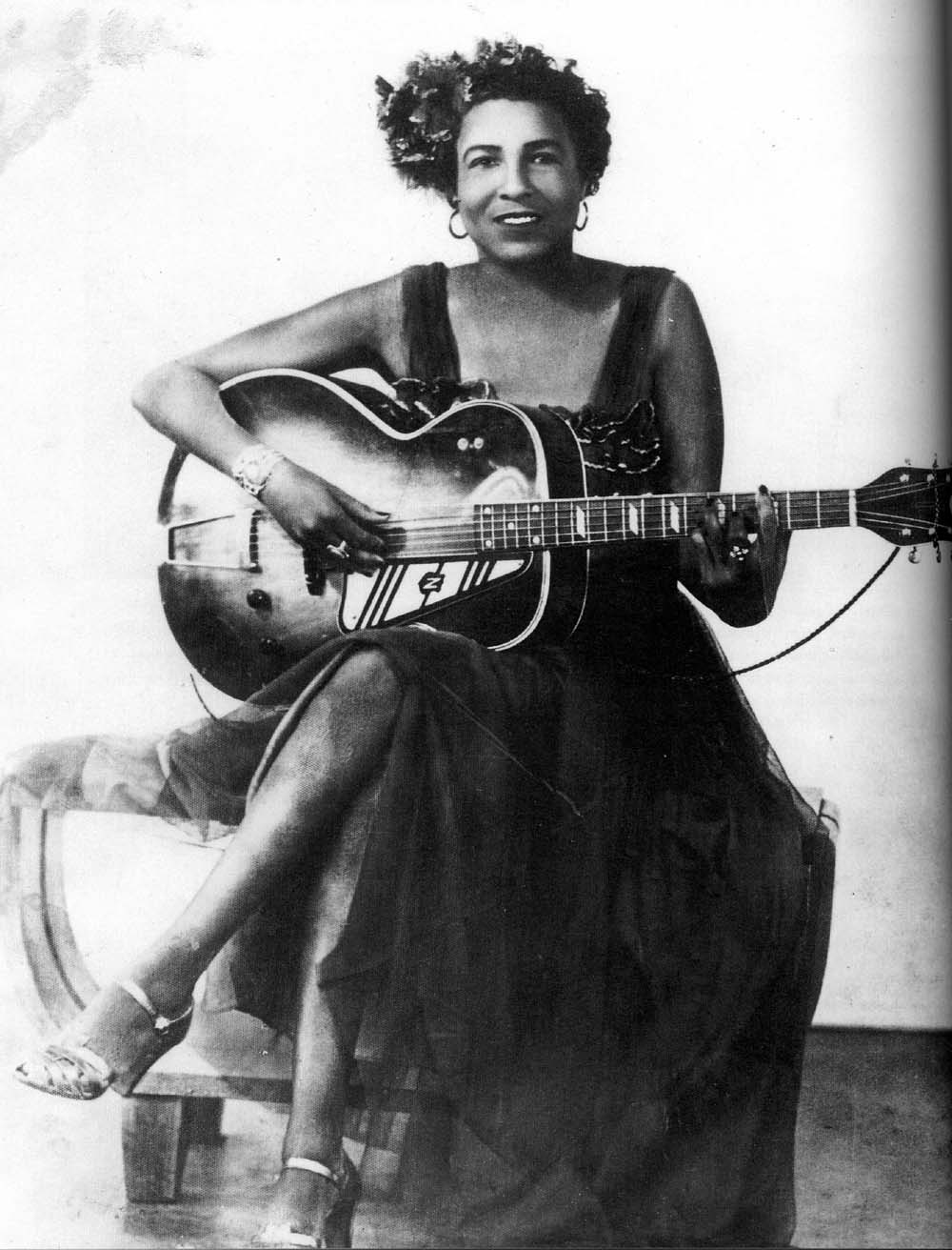 Memphis Minnie sitting with a guitar.
