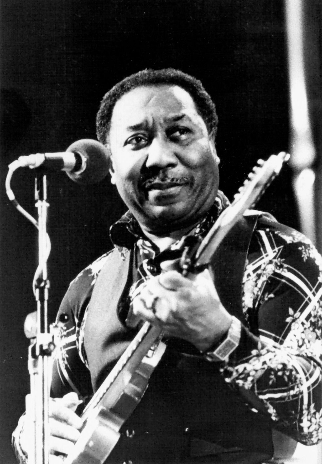 Photo of Muddy Waters playing the guitar.